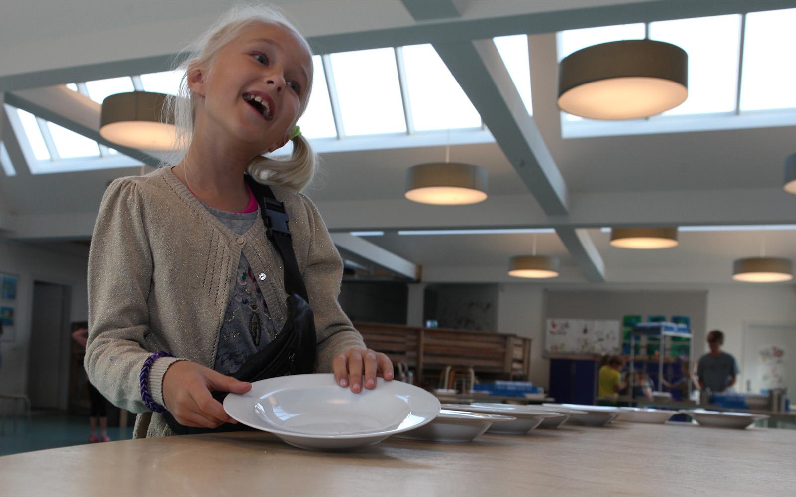 Schülerin in der mit Dachverglasung und künstlicher Beleuchtung belichteten Cafeteria