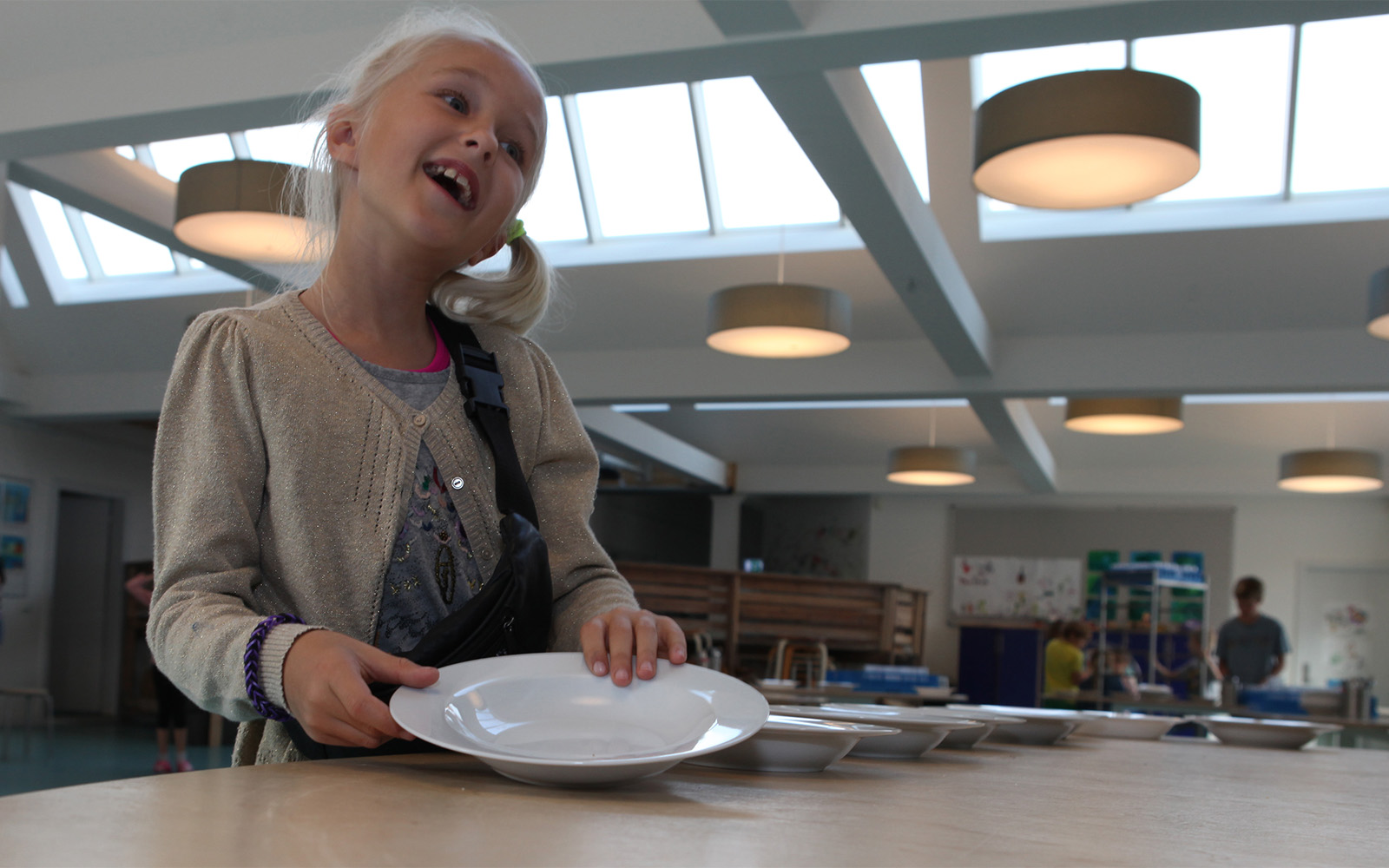 Écolière à la cafétéria, illuminée grâce aux verrières et un éclairage artificiel