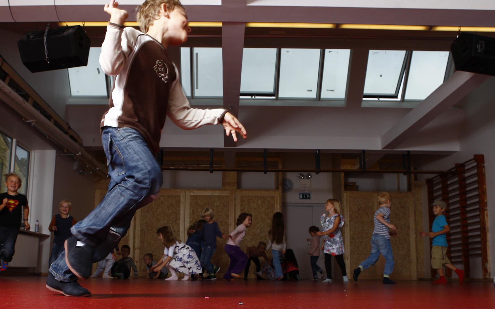 Écoliers jouant dans un gymnase illuminé grâce à une verrière de toit